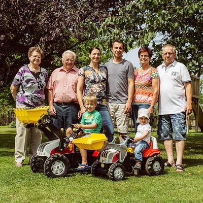 Familie Vogler im Garten, Kinder sitzen auf Tret-Traktoren davor