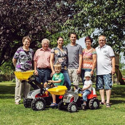 Familie Vogler steht im Garten und zwei Kinder sitzen auf Tret-Traktoren davor