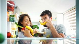Mann und Frau stehen vor Kühlschrank mit Obst und Gemüse