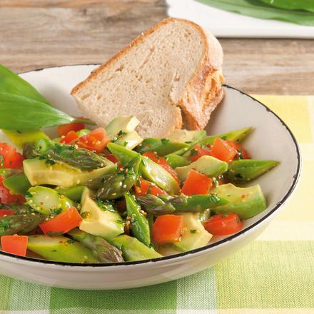 Salat mit grünem Spargel, Avocados und Tomaten serviert auf einem tiefen weißen Teller und garniert mit einer halben Scheibe dunklem Bauernbrot