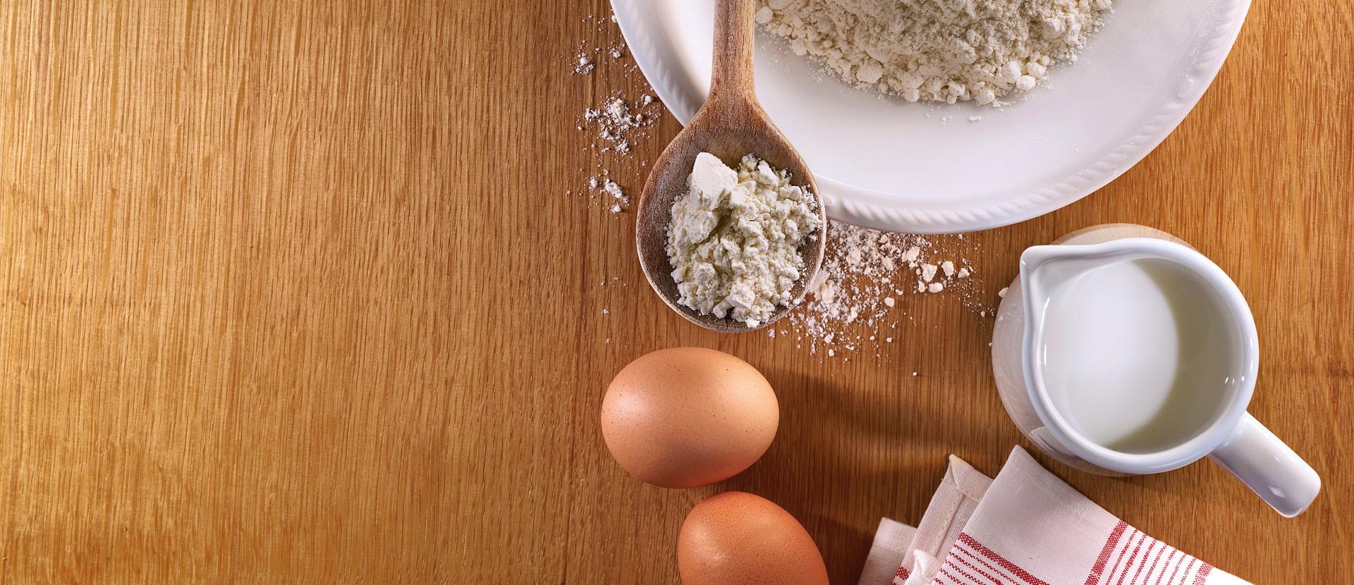Mehl in Schüssel mit Milch und Eiern