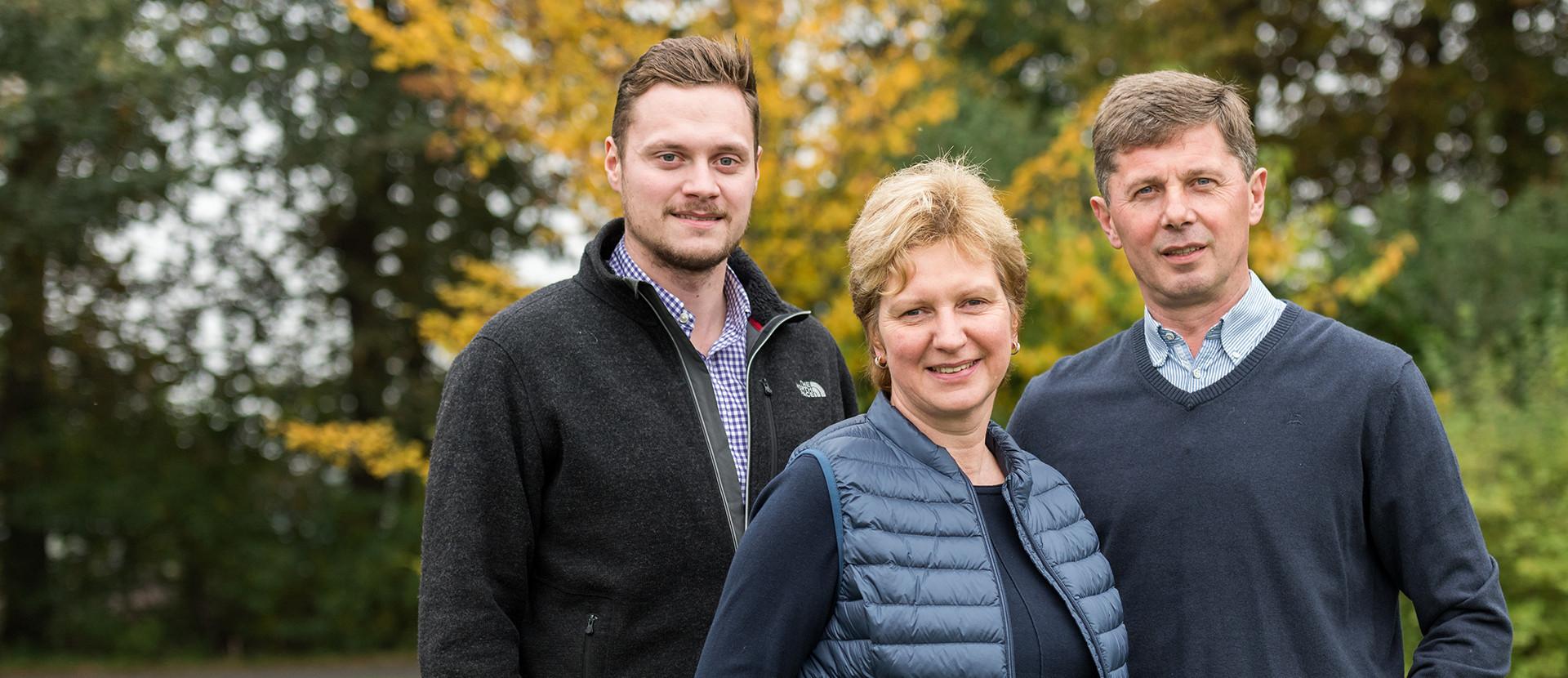 Betriebsfamilie, zwei Männer und eine Frau, vor unscharfen Bäumen