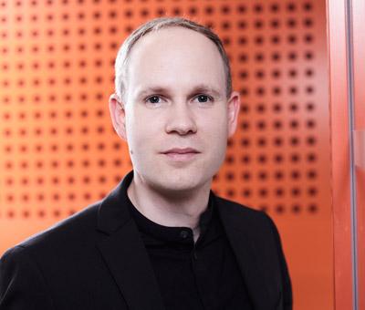 Benjamin Braehler vor orangener Wand