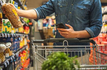 Mann mit Handy und Nudelpackung beim Einkaufen im Markt