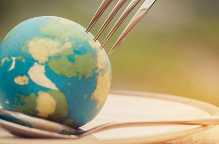 Weltkugel auf einem Teller mit Gabel und Löffel