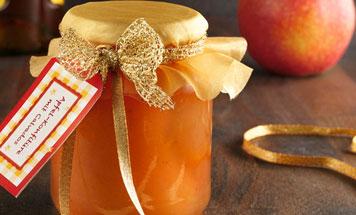Apfelkonfitüre mit Calvados im Einmachglas als Geschenk verpackt