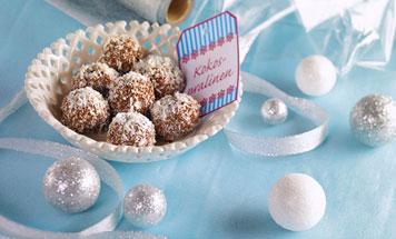Kokospralinen in Porzellanschale auf hellblauem Tuch