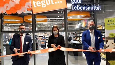 Drei Personen zerschneiden Band bei Neueröffnung in München.