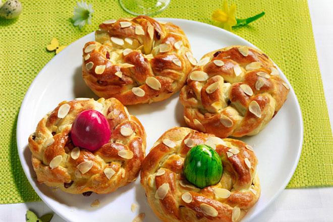vier Oster-Hefekränze mit bunten Eiern