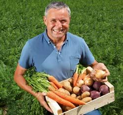 Bauer Schwab mit einer Kiste Gemüse in den Händen auf einem Feld