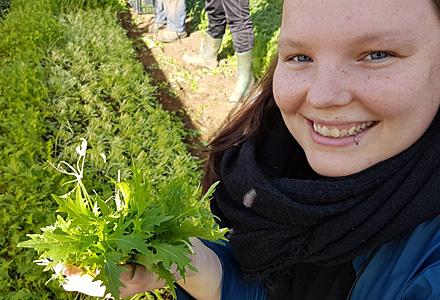 Bio-Botschafterin mit Rucola auf einem Feld