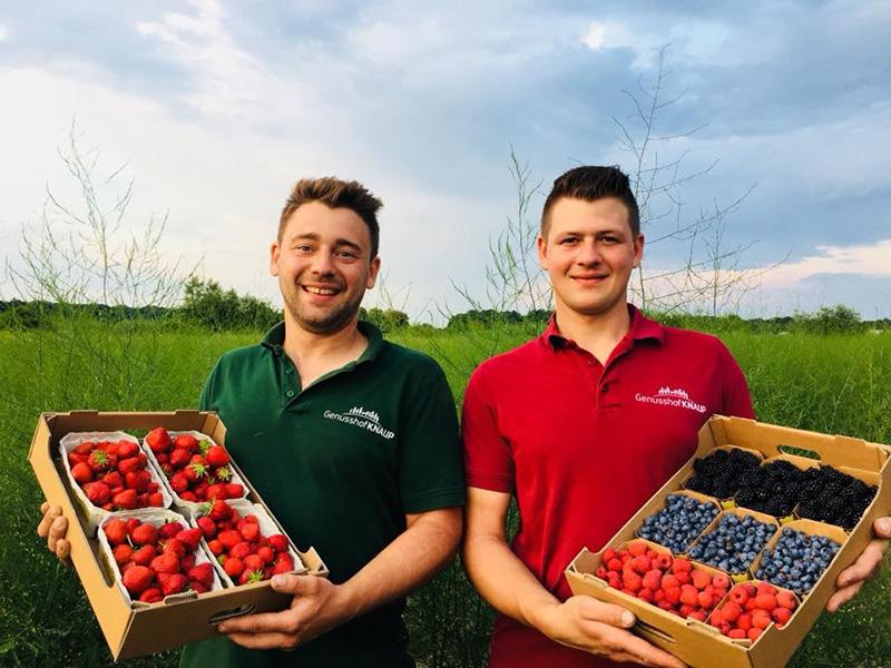 Die zwei Brüder Knaup präsentieren Erdbeeren, Himbeeren, Brombeeren und Heidelbeeren in Kisten