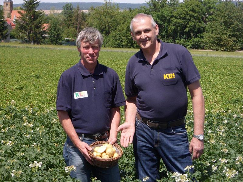 Zwei Männer mit Kartoffeln auf einem Kartoffelacker