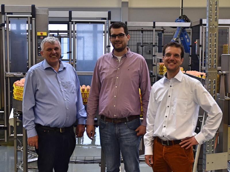 Die Geschäftsführung, drei Männer, stehen vor einem Förderband, welches Eier in einen Lagerraum transportiert