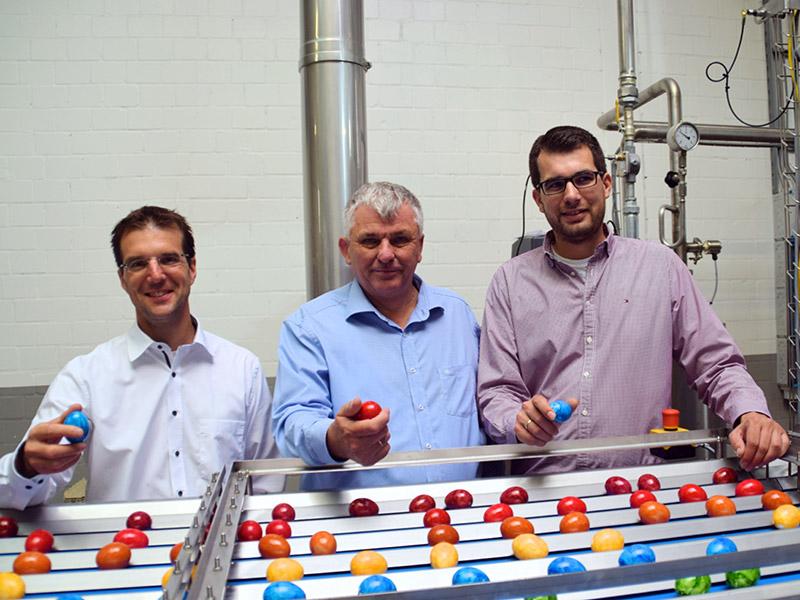 Drei Mitarbeiter stehen in der Färberei hinter einem Förderband mit bunten gefärbten Eiern, jeder hält ein Ei in der Hand