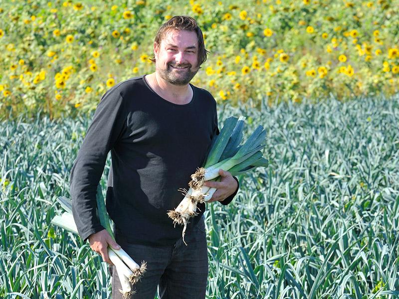 Der Betriebsleiter steht vor einem Lauch- und Sonnenblumenfeld und hält frisch geerntete Lauchstangen in seinen Händen