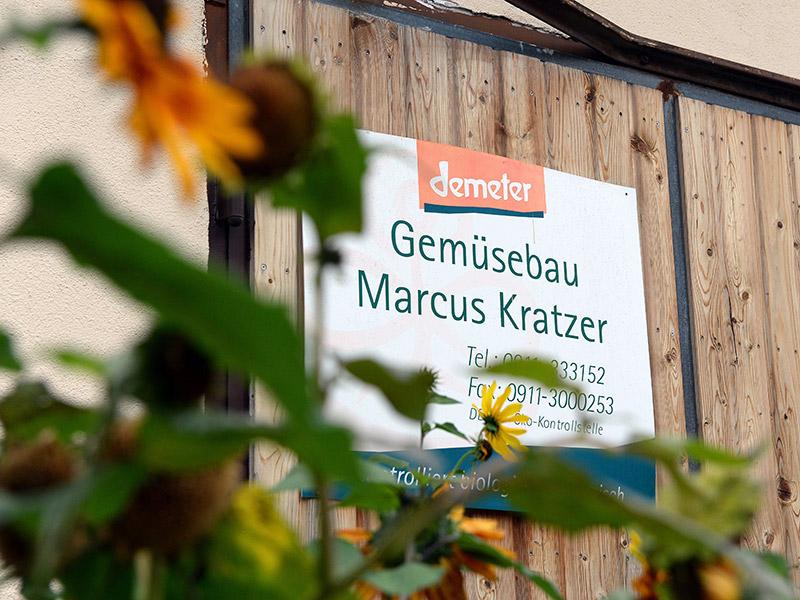 """Das Betriebsschild """"Gemüsebau Marcus Kratzer"""" hängt an einem Scheunentor, im Vordergrund sind unscharfe Sonnenblumen zu erkennen"""
