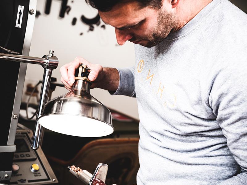 Mann bei der Qualitätssicherung der Kaffeebohnen.