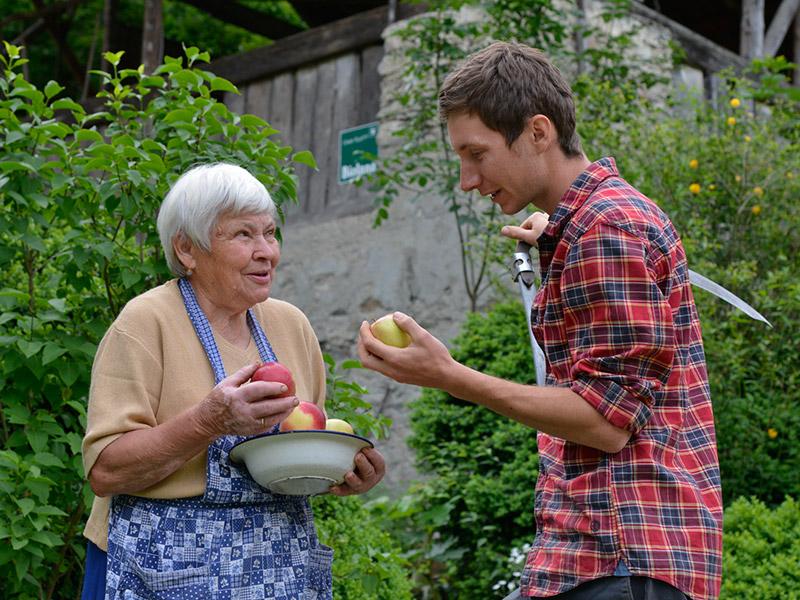 Eine ältere Frau hält in einer Hand eine Schale mit Äpfeln und in der anderen einen einzelnen Apfel, daneben steht ein junger Mann, der ebenfalls einen Apfel in der Hand hält