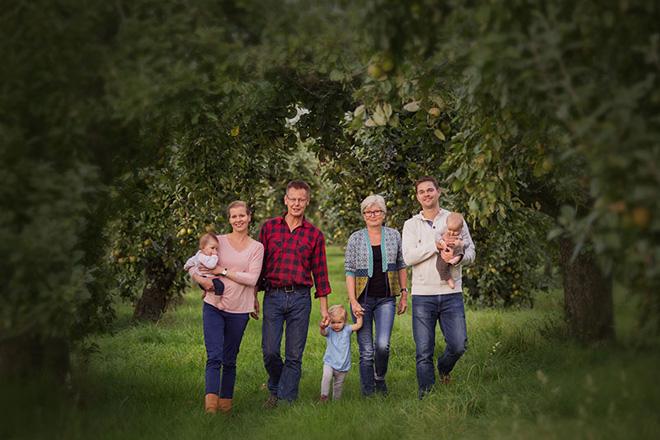 Familie Münch, vier Erwachsene und drei Kleinkinder, zwischen Apfelbäumen