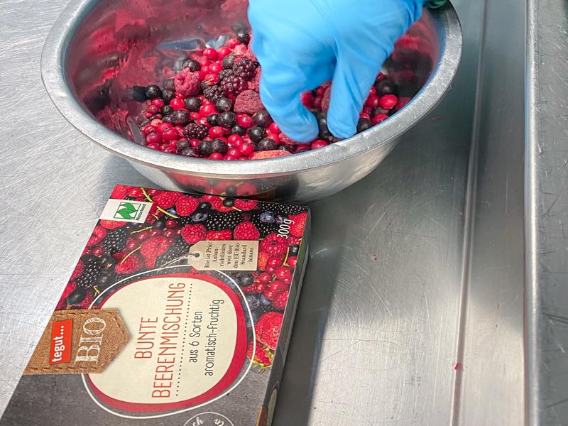 Beerenmischung in Schüssel und in Produktverpackung