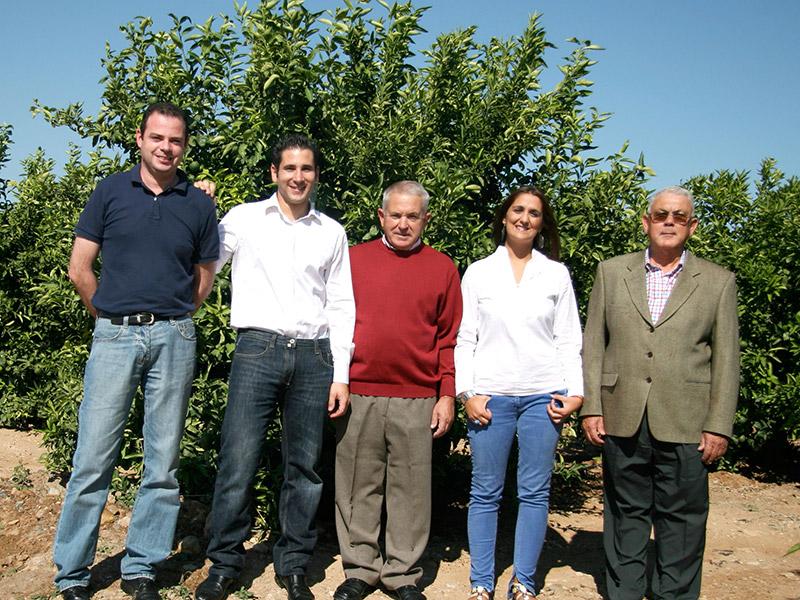 Das Team steht vor einem Zitrusfruchtbaum