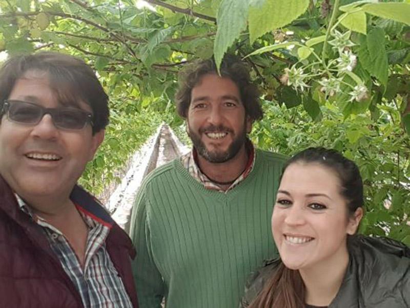 Mitarbeiter und Mitarbeiterinnen zwischen zwei Pflanzreihen Beerensträucher