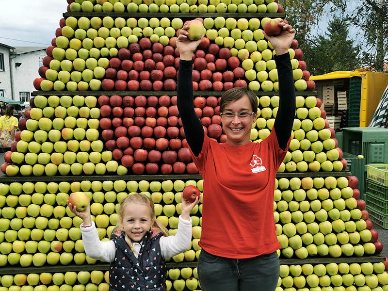 Eine Frau und ein Kind halten Äpfel in die Luft