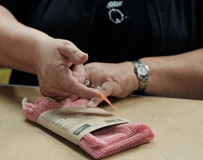 Näherin klebt Aufkleber auf Manomama Bio Baumwollnetz