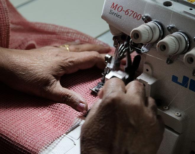 zwei Hände mit Bio-Baumwollnetz beim Nähen mit Nähmaschine