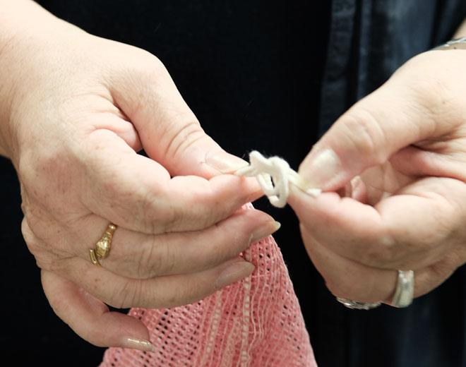 Zwei Hände knoten Manomama Bio Baumwollnetz
