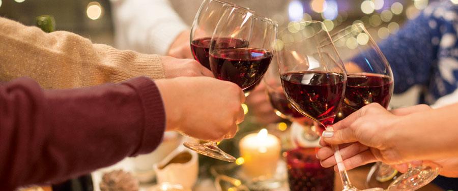 Hände stoßen mit Weingläsern an