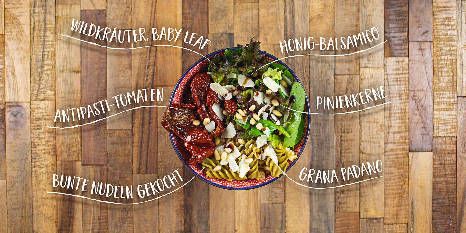Salat Bowl mit Wildkraueter, Baby Leaf, Antipasti Tomaten, bunte Nudeln, Pinienkerne, Grana Padano und Honig Balsamico Dressing