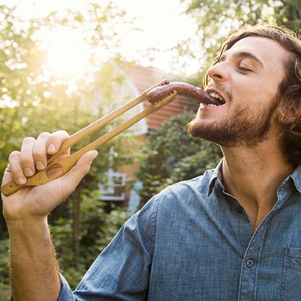 Mann isst Wurst mit Grillzange