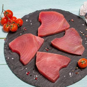 Fisch auf einem runden Brettchen mit Tomaten daneben