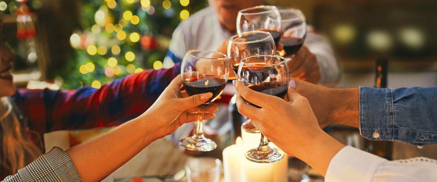 Hände stoßen mit Rotweinglässer an