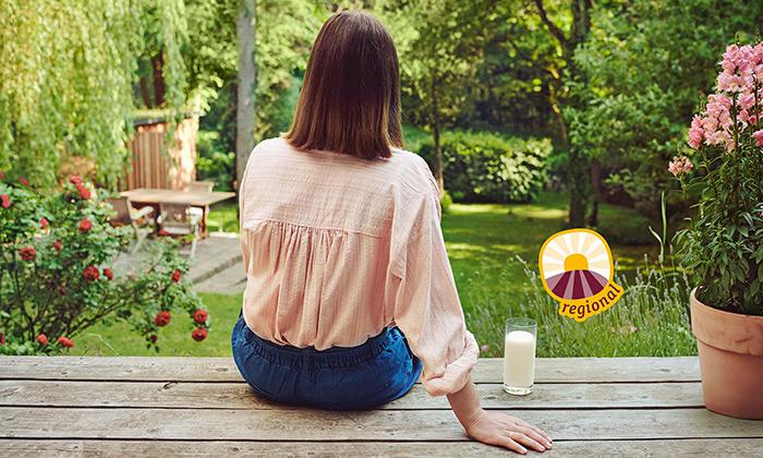 Frau auf Holzterreasse sitzend mit Milchglas tegut Sonnensymbol regional