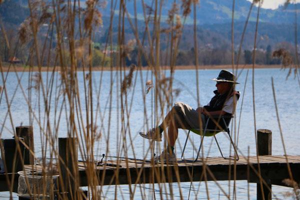 Fischer sitzt auf einem Steg an einem See