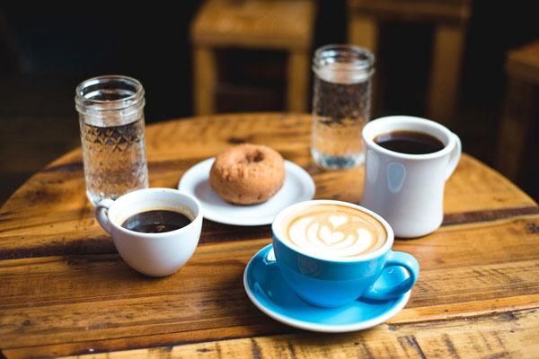 Tisch mit Kaffee, Wasser und Brötchen