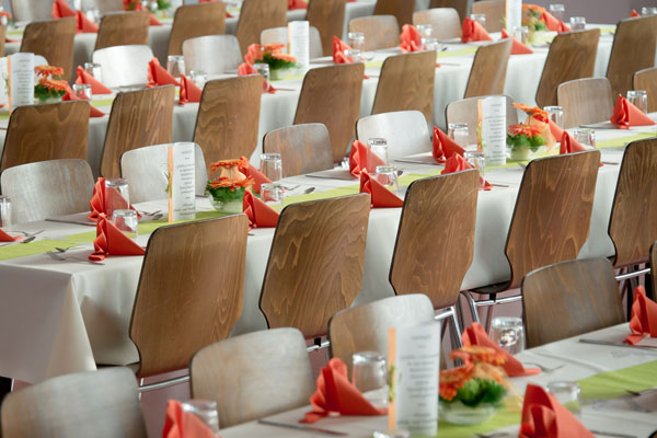 eingedeckte Tische mit Stühlen