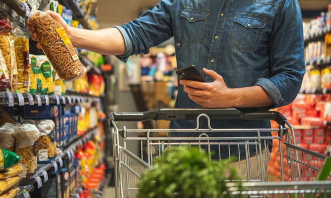 Nachhaltig Einkaufen Mann mit Einkaufswagen und Handy