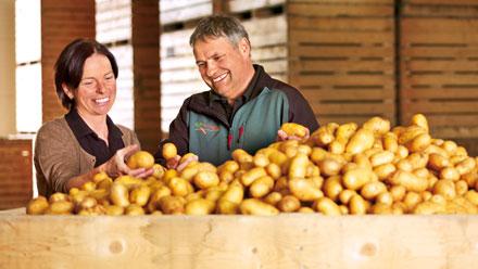 Bauer und Frau stehen vor großer Holzkiste mit Kartoffeln