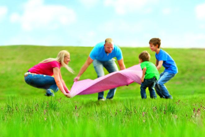 Familie legt Decke auf Wiese