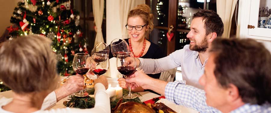 Familie stößt mit Weingläsern an einem Tisch an