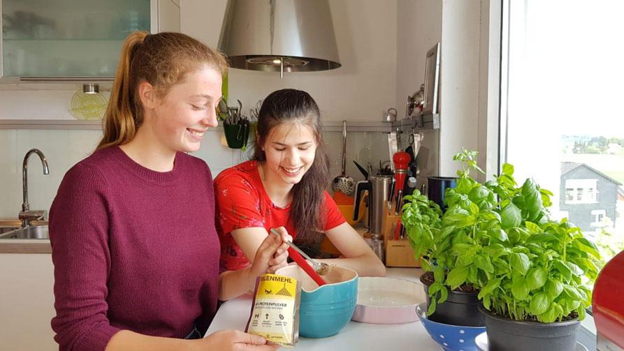 zwei Mädchen in der Küche bereiten Insekten-Pasta zu