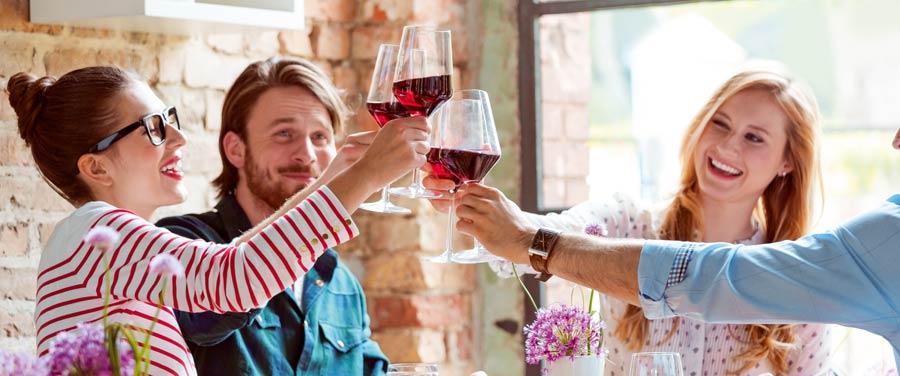 Zwei Paare sitzen am Tisch und stoßen mit Weingläsern an