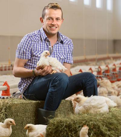 Landwirt mit Hühner im Stall