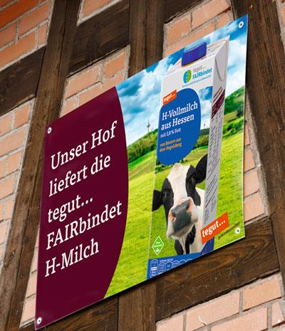 Plakat an Scheunenwand mit fairbindet H-Milch
