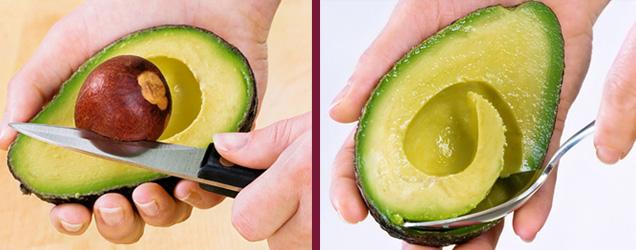 Hände die den Kern der Avocado mit Messer und Löffel rauslösen