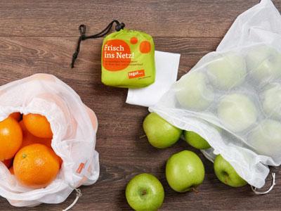 weißes Netz gefüllt mit Orangen und Äpfeln
